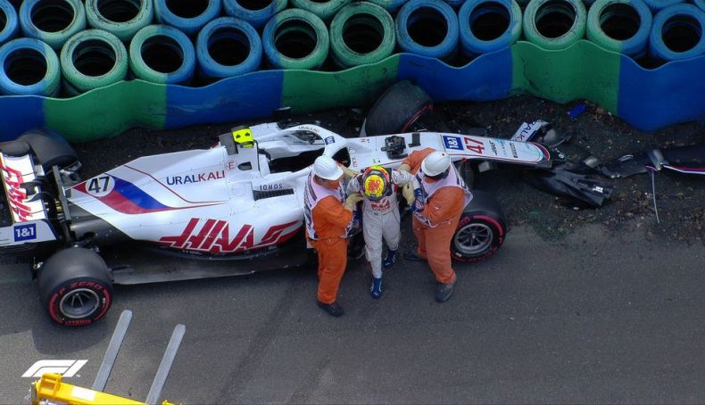 Mick Schumacher is helped out of his car after the accident