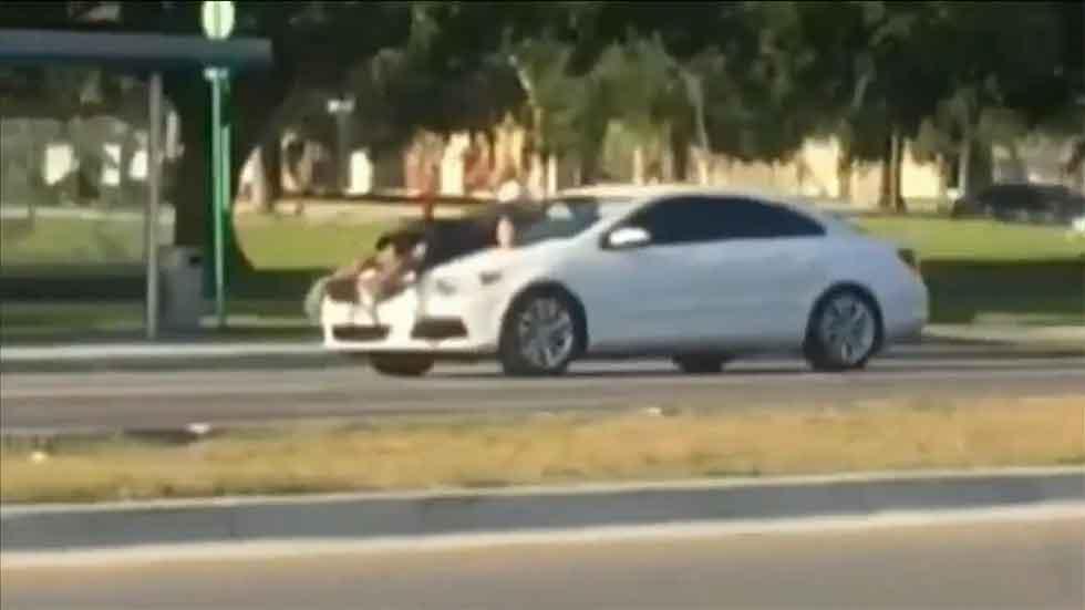 Conduce a toda velocidad con un hombre encaramado en el capó (vídeo)