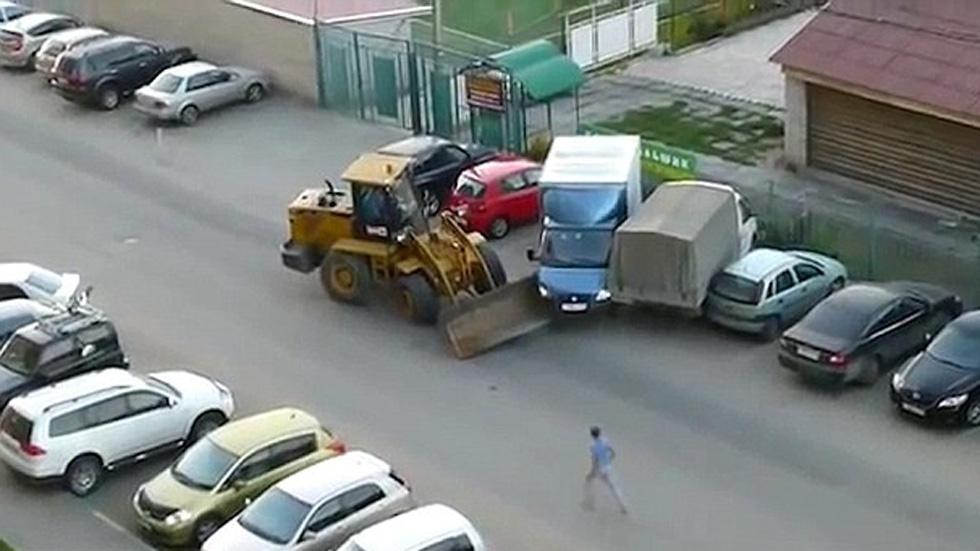 Una excavadora arremete contra varios coches (vídeo)