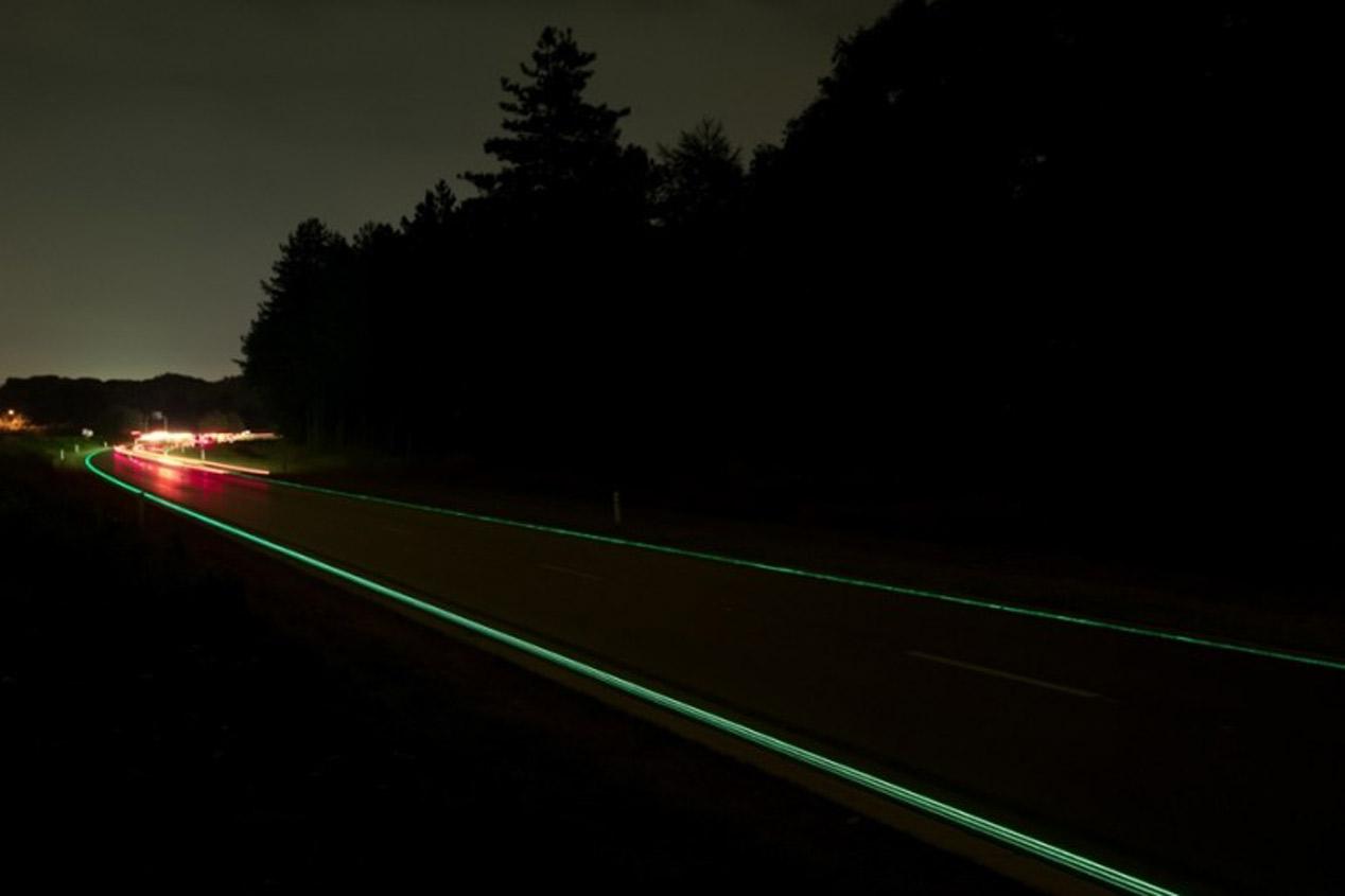 Carretera con marcas viales que brillan en la oscuridad